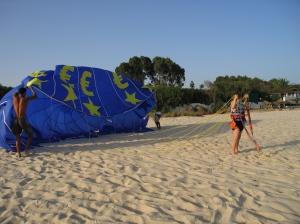 girl hang gliding on beach