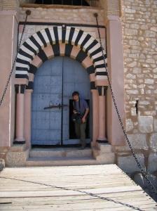Student emerging from traditional Tunisian door within a door